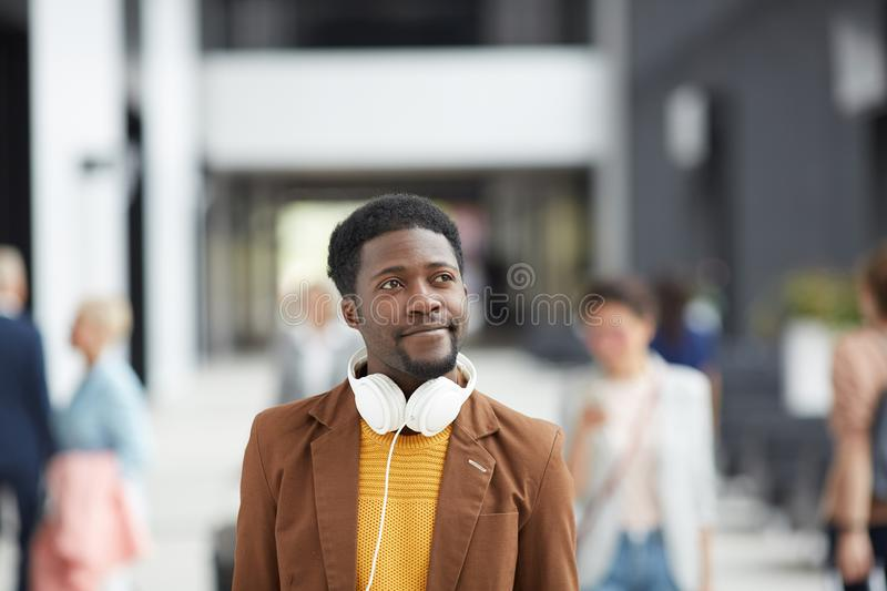 Modern guy in crowded lobby. Content dreamy modern Afro-American guy with headphones crossing crowded lobby and planning vacation stock photo