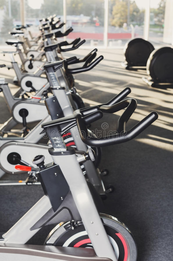 Modern gym interior with equipment, fitness exercise bikes handlebars stock image