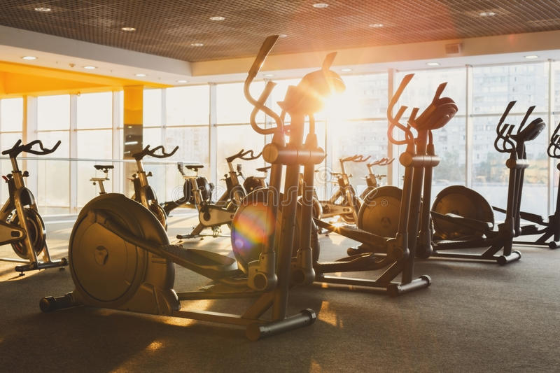 Modern gym interior with equipment, fitness exercise elliptical trainers royalty free stock photos