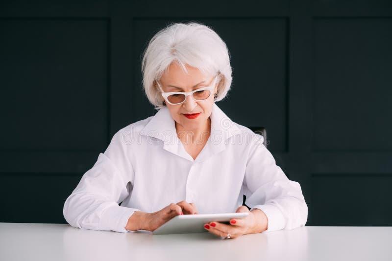 Modern hög livsstil för äldre kvinnastående royaltyfri foto