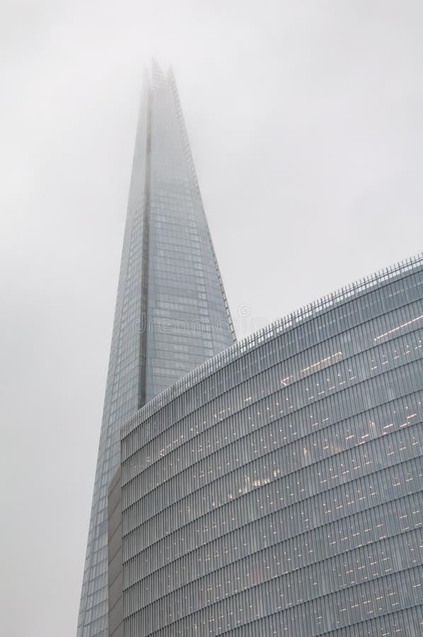 Modern högväxt skyskrapabyggnad i dimmig dimma arkivfoton