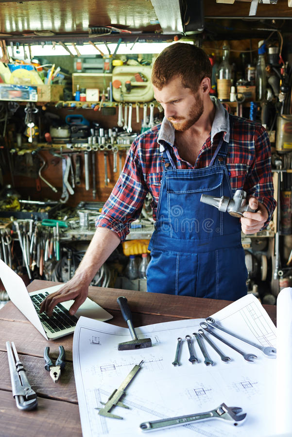Modern Handsome Mechanic Working in Garage royalty free stock photography