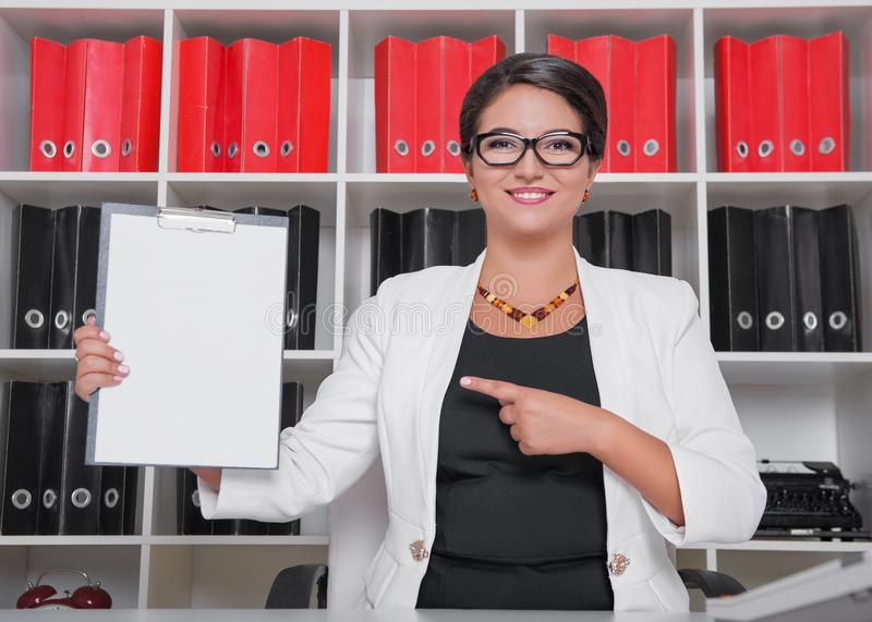 Modern happy beautiful business woman showing on blank paper royalty free stock photography