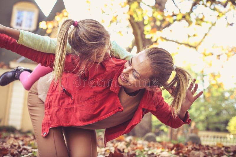 Modern har lek med barnet som bär henne på på ryggen royaltyfri foto