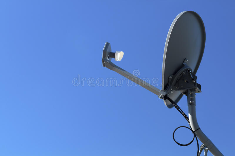 Modern HD Satellite Dish On A Clear Blue Sky Day. Modern HD satellite dish mounted on a grey metal pole on a clear blue sky day royalty free stock photography
