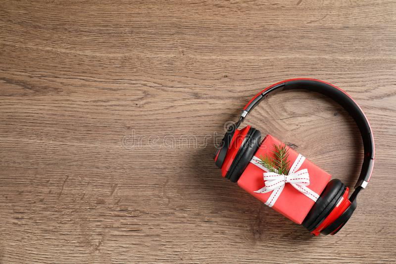 Modern headphones and gift on wooden background, top view with space for text. Christmas music concept. Modern headphones and gift box on wooden background, top royalty free stock images