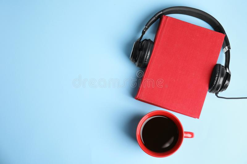 Modern headphones with hardcover book and coffee on blue background, top view. Space for text royalty free stock photos