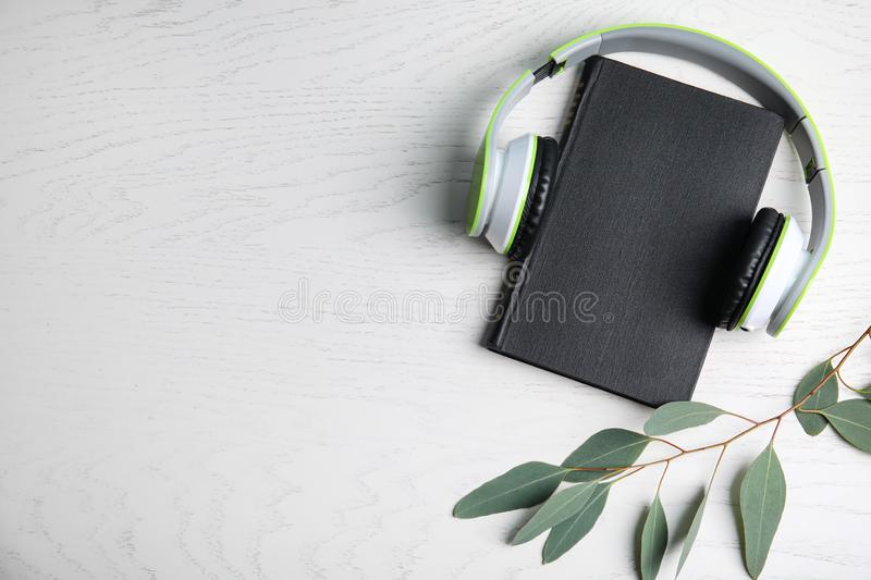 Modern headphones with hardcover book on wooden background, top view. Space for text. Modern headphones with hardcover book on white wooden background, top view royalty free stock images