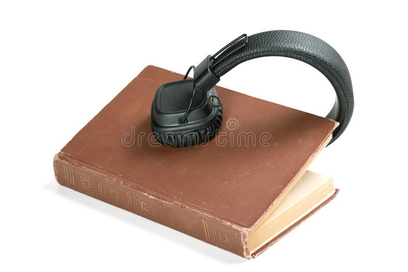 Modern headphones on an old book. White background royalty free stock image