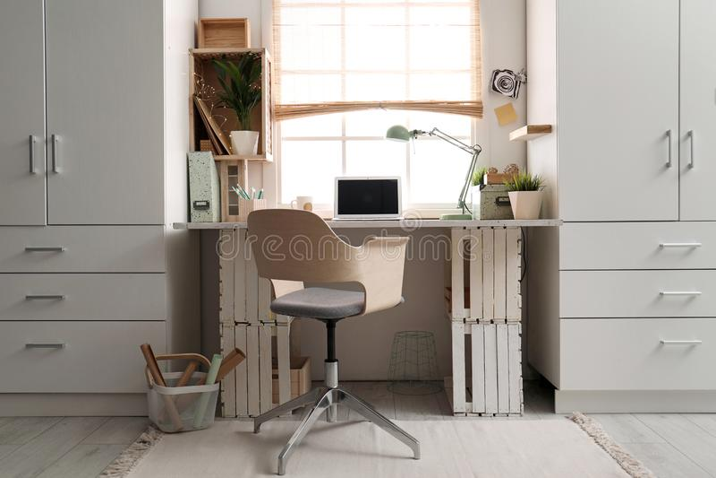 Modern hem- arbetsplats med träspjällådor arkivfoto