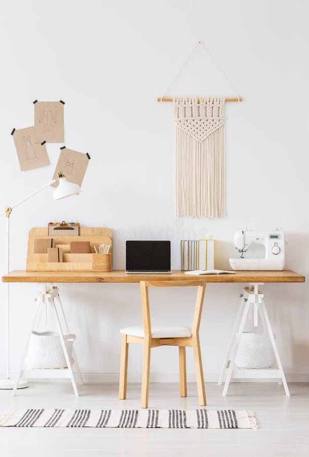 Modern hem- offficeinre med ett skrivbord, en bärbar dator, en symaskin, en stol och en makramé på en vägg Tom skärm, ställe arkivbilder
