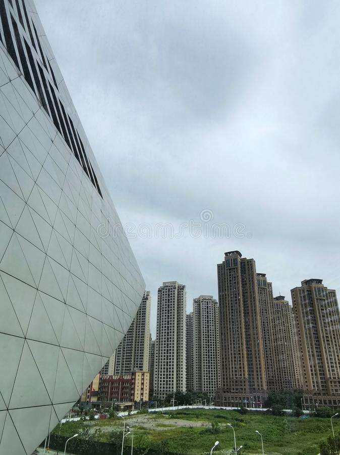 Modern high building with overcast sky. Modern high building with green lawn and overcast sky in wuhan city, china royalty free stock photos