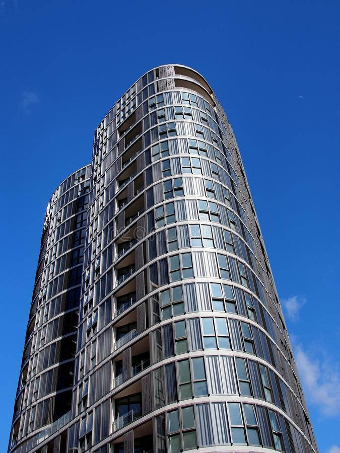 Modern High Rise Apartment Building. A new high rise apartment or condominium building, with rounded towers and enclosed balconies royalty free stock images