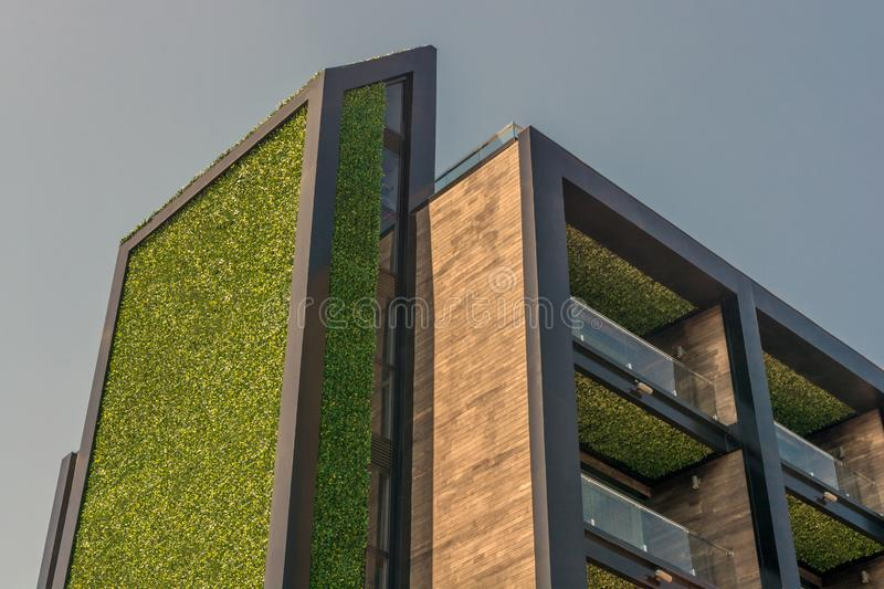 Modern high-rise building. Beautiful architecture. Green elements in high-tech style. Balconies on the facade and terrace on the royalty free stock image