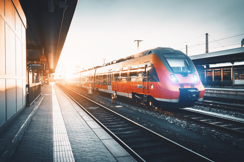 Modern high speed red commuter train at the railway station. At sunset. Turning on train headlights. Railroad with vintage toning. Train at railway platform royalty free stock photography