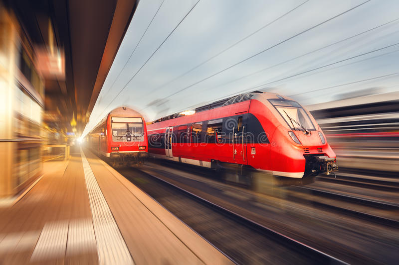 Modern high speed red passenger trains at sunset. Railway station. In Nuremberg, Germany. Railroad with motion blur effect. Industrial concept landscape stock photography