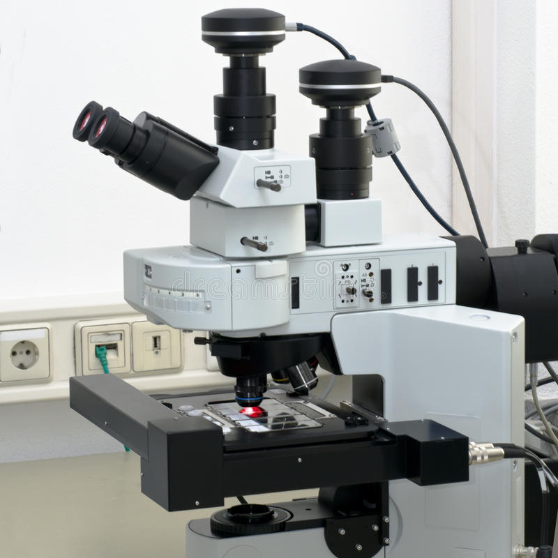 Modern high throuput fluorescent microscope. Scanning several biopsy samples royalty free stock images