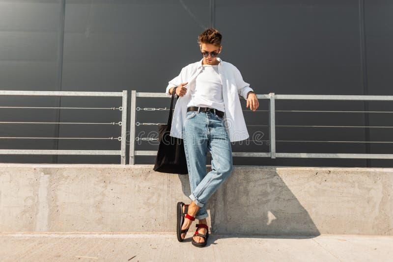 Modern hipster för ung man i vit kläder för trendig sommar i solglasögon i stilfulla röda lädersandaler med ställningar för en på royaltyfria foton