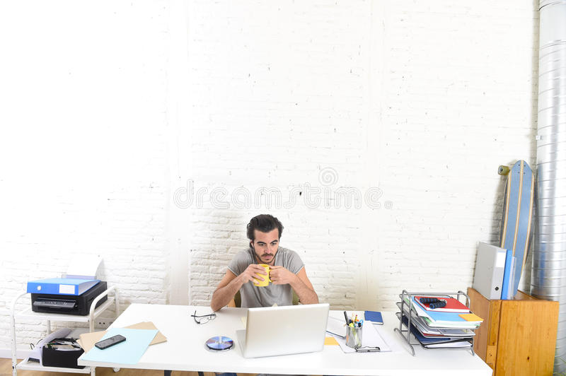 Modern hipster style student or businessman working with laptop computer at home office drinking coffee cup. Young modern hipster style student or businessman royalty free stock photo