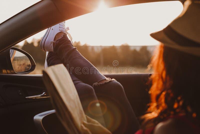 Modern hipstermeisje die in een auto rusten en een kaart lezen Vrouw met voeten op autodeur Voeten buiten het venster bij zonsond royalty-vrije stock foto's