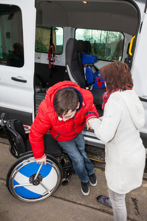 Modern hjälper hennes handikappade son av skolbussen royaltyfri bild