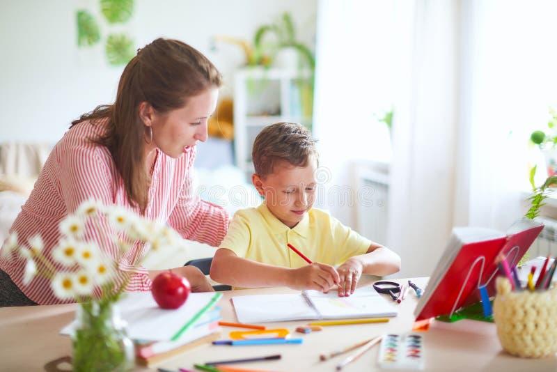 Modern hjälper sonen att göra kurser hem- skolgång, hem- kurser handleda kopplas in med barnet, undervisar för att skriva och räk royaltyfria foton