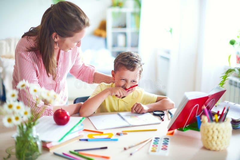 Modern hjälper sonen att göra kurser hem- skolgång, hem- kurser handleda kopplas in med barnet, undervisar för att skriva och räk arkivbilder