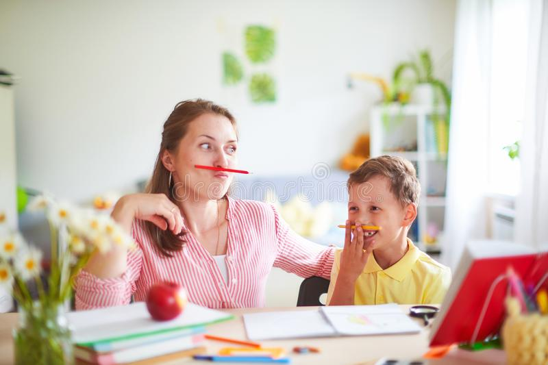 Modern hjälper sonen att göra kurser hem- skolgång, hem- kurser kvinnan kopplas in med barnet, kontroller det gjorda jobbet utanf royaltyfri fotografi