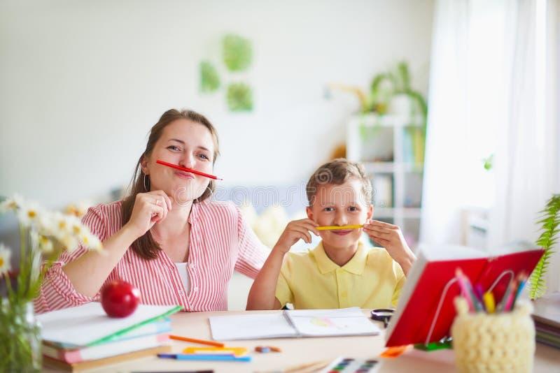 Modern hjälper sonen att göra kurser hem- skolgång, hem- kurser kvinnan kopplas in med barnet, kontroller det gjorda jobbet utanf royaltyfria bilder