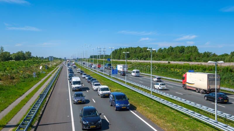 Modern holländsk fördjupad huvudväg A4, eftermiddagtrafikstockningriktning Rotterdam, Nederländerna royaltyfria foton