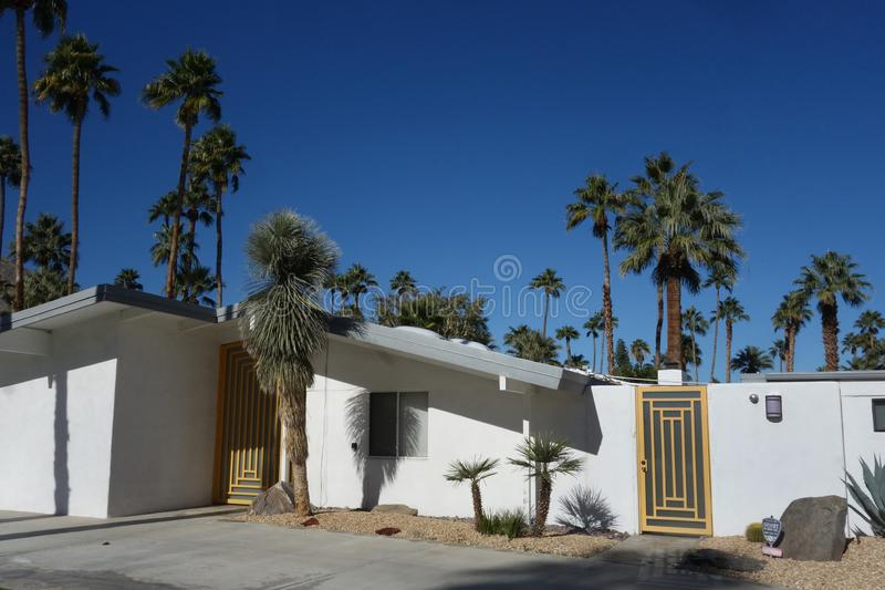 Modern Home in Palm Springs. Modern home with butterfly roof and gold modern designed door in Palm Springs, California royalty free stock images