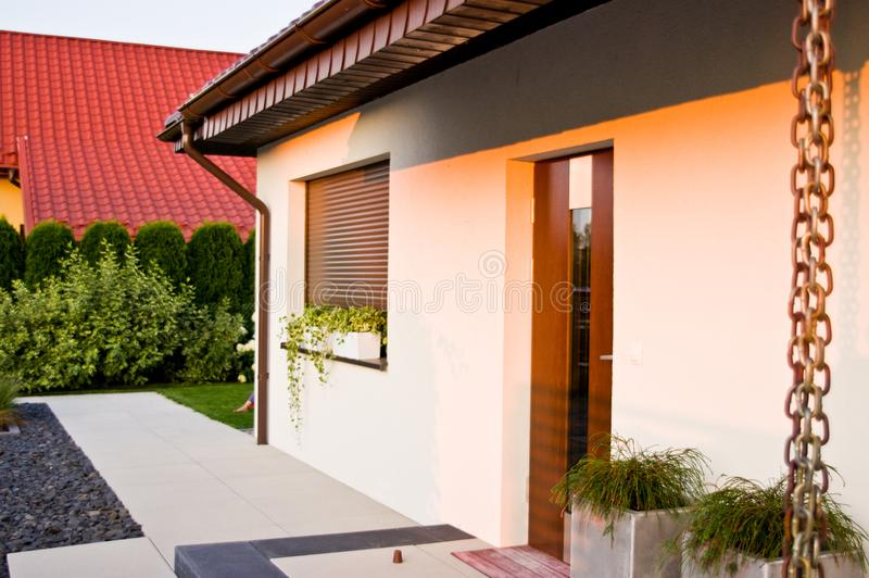 Modern home or house entrance door with rainchain in summer. stock photos