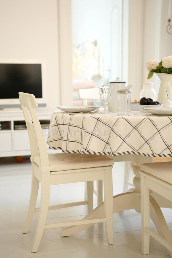Modern home interior. Table and the dishes in the dining room royalty free stock image