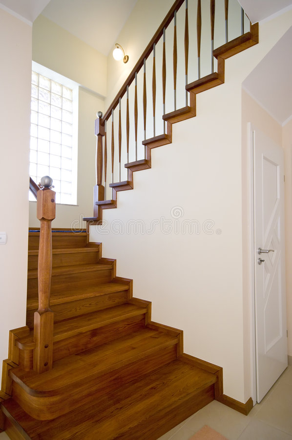 Modern home interior. Modern house interior design, brown wooden stairs and the door to a storage room underneath