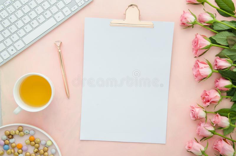 Modern home office desk workspace with blank paper clipboard, pink roses flower bouquet,keyboard, herbal tea, rose gold royalty free stock images