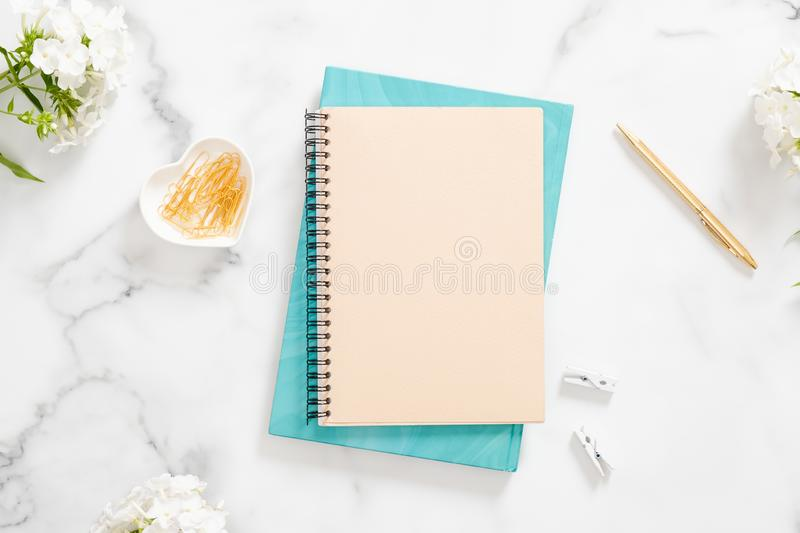 Modern home office desk workspace with blank paper notebook, white flowers and feminine accessories on marble background. Flat lay royalty free stock photos