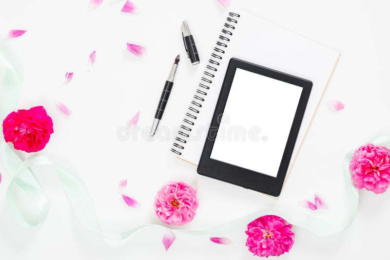 Modern home office desk workspace with blank screen tablet e-book, feminine accessories, blue mint ribbon, pink rose flower buds. And petal on white background royalty free stock photo