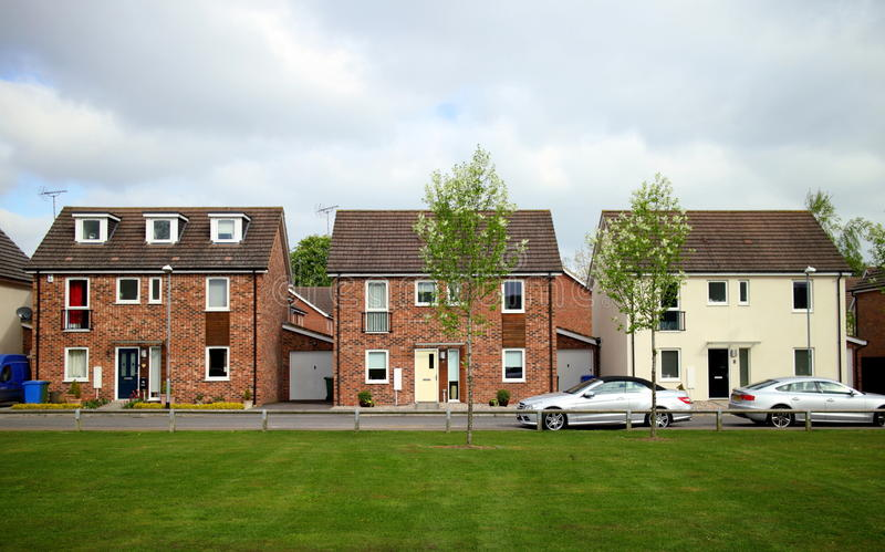 Modern Homes in England. Bracknell, England - April 12, 2017: Front view of detached houses in a row with cars outside and a green space in front on a modern stock image