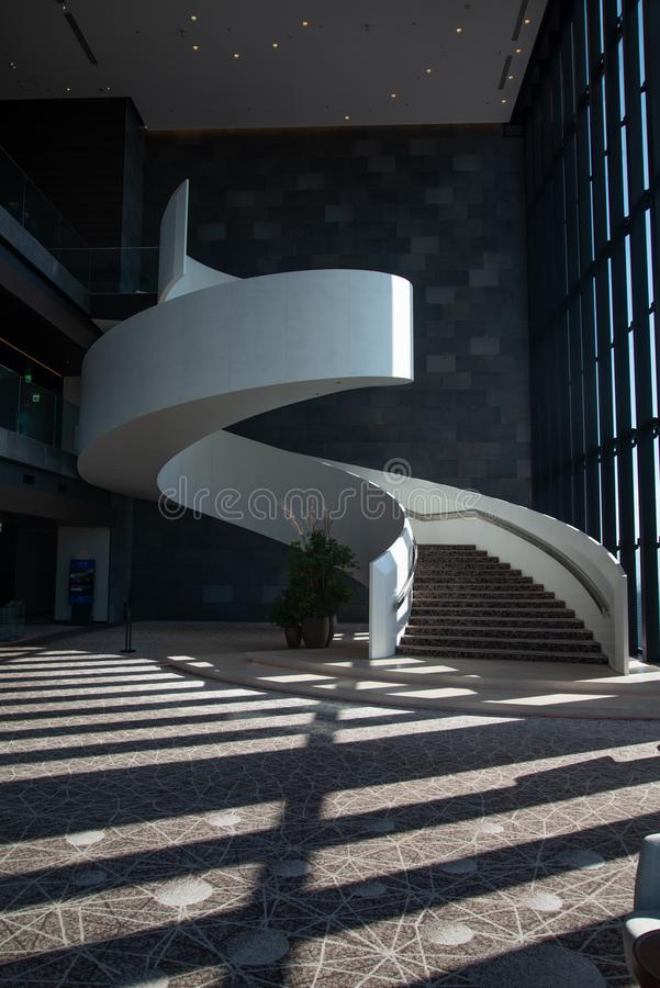 Modern hotel architecture. Lobby staircase. Contemporary architecture, Japanese hotel. White grand spiral staircase in an hotel lobby. Light and shadow effect stock photography