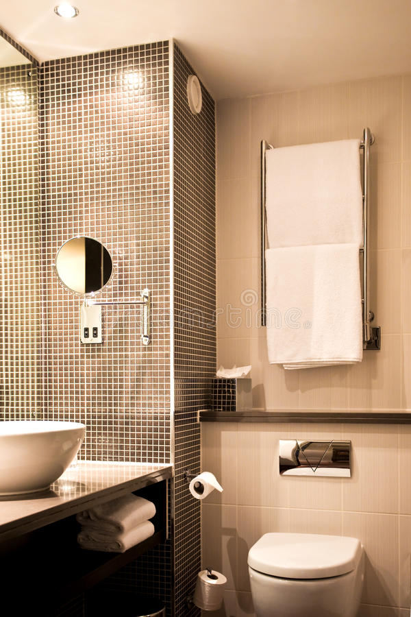 Modern hotel bathroom. With sink mirror, tiles and toilet royalty free stock photography