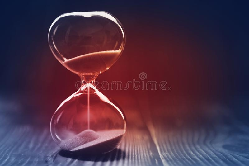 Modern Hourglass with dark background, sand trickling through the bulbs of a crystal sand glass, with red light in the center. Lost time concept royalty free stock photo