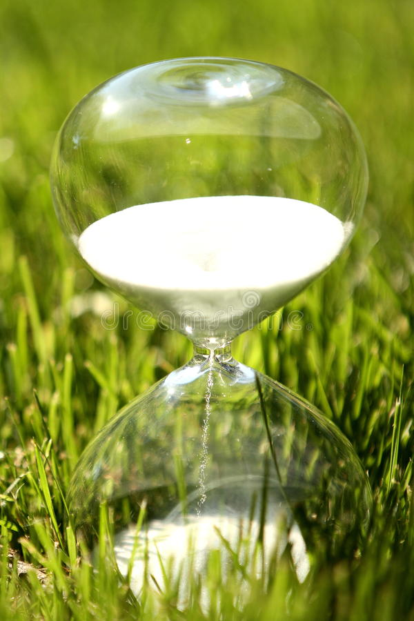 Modern hourglass on green background. Symbol of time stock image