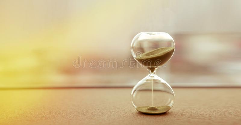 Modern hourglass with sand color background, as time passing concept for business deadline, urgency and running out of time stock images