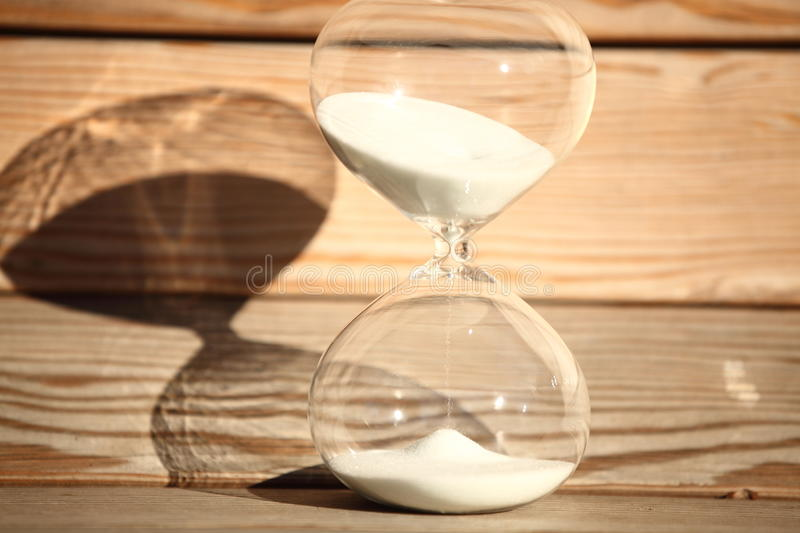 Modern Hourglass. symbol of time. countdown. Modern Hourglass -- sand trickling through the bulbs of a crystal sand glass. symbol of time. countdown. Time stock photography