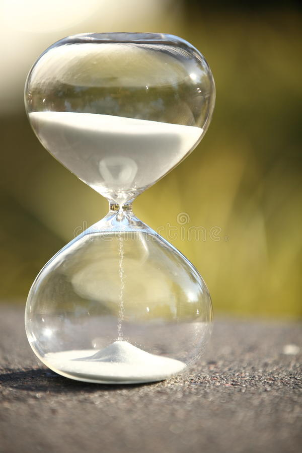 Modern Hourglass. symbol of time. countdown. Modern Hourglass -- sand trickling through the bulbs of a crystal sand glass. symbol of time. countdown. Time stock images