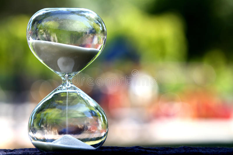 Modern Hourglass. symbol of time. countdown. Modern Hourglass -- sand trickling through the bulbs of a crystal sand glass. symbol of time. countdown. Time royalty free stock images