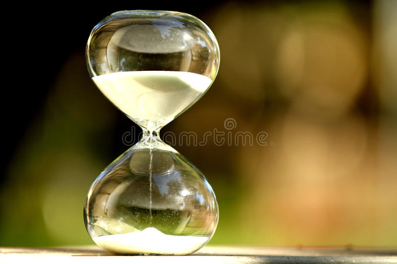 Modern Hourglass. symbol of time. countdown. Modern Hourglass -- sand trickling through the bulbs of a crystal sand glass. symbol of time. countdown. Time stock photo