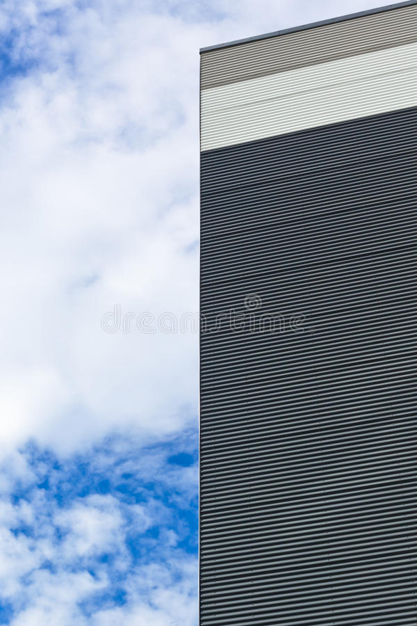 Modern house abstract part. Part of new house with vinyl siding against blue sky in the background stock photo