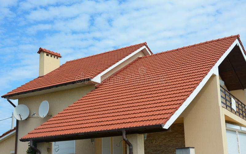Modern house with chimney, red clay tiled roof and gable and valley type of roof construction. Building attic house construction royalty free stock image