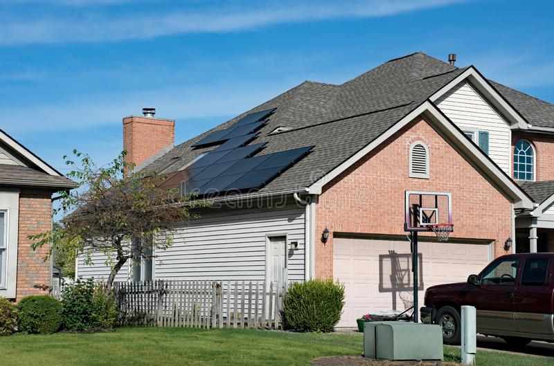Energy Efficient Home with Roof Solar Panels. Modern house with energy efficient solar panels mounted to garage roof stock image